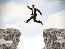 Funny business man jumping over rocks with gap Stock Images