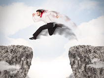 Funny business man jumping over rocks with gap Royalty Free Stock Photo