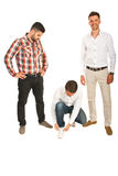 Funny business men. One businessman wondering and looking at a colleague who tying shoe laces and the other laughing isolated on white background Stock Image