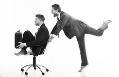 Funny business, success concept. Business people have fun and ride on office chair. Businessman pushing male colleague in chair on white background. Coworkers stock photo