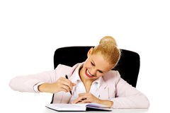Funny business woman taking notes behind the desk Stock Photo
