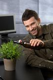 Funny businessman. Funny young businessman pretending to water potted plant from beer bottle in office Royalty Free Stock Image