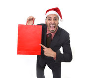Funny businessman in Christmas Santa hat holding red shopping bag in December and New year sale Royalty Free Stock Images