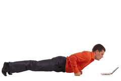Funny businessman doing push-ups. Looking on laptop screen royalty free stock images