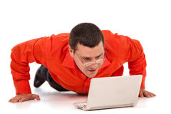 Funny businessman doing push-ups. Looking on laptop screen Royalty Free Stock Image