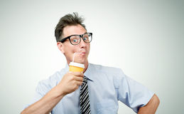 Funny businessman drinking from a paper cup with a straw Royalty Free Stock Images
