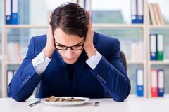 The funny businessman eating gold coins in office. Funny businessman eating gold coins in office stock image
