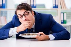 The funny businessman eating gold coins in office. Funny businessman eating gold coins in office stock photo