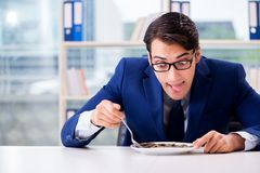 The funny businessman eating gold coins in office. Funny businessman eating gold coins in office royalty free stock photo
