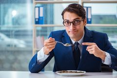 The funny businessman eating gold coins in office. Funny businessman eating gold coins in office royalty free stock photos