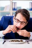 The funny businessman eating gold coins in office. Funny businessman eating gold coins in office royalty free stock photography