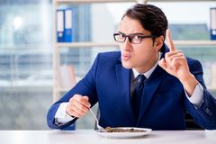 The funny businessman eating gold coins in office. Funny businessman eating gold coins in office royalty free stock images