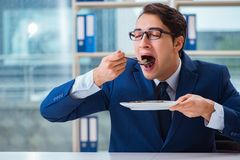 The funny businessman eating gold coins in office. Funny businessman eating gold coins in office stock images