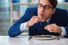 The funny businessman eating gold coins in office. Funny businessman eating gold coins in office royalty free stock image