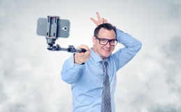 Funny businessman in glasses making selfie with a stick.  Royalty Free Stock Photos