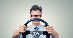 Funny businessman in glasses with a steering wheel. Car drive concept Royalty Free Stock Photo
