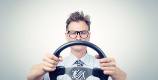 Funny businessman in glasses with a steering wheel, car drive concept. On background royalty free stock photo
