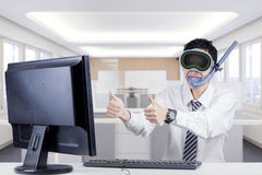 Funny businessman with goggles in office. Portrait of a funny businessman wearing goggles and snorkel in the office, showing thumbs up on the monitor Royalty Free Stock Image