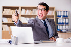 The funny businessman with gun in office Stock Images