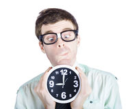 Funny businessman holding clock at rush hour time Royalty Free Stock Image