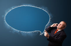 Funny businessman holding a phone and presenting speech bubble c Royalty Free Stock Image