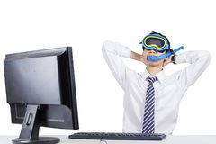 Funny businessman imagining his vacation. Funny businessman wearing snorkeling equipment while working with computer and imagining his vacation, isolated on Stock Photo