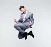 Funny businessman jumping in air. Funny cheerful businessman jumping in air over gray background Stock Image