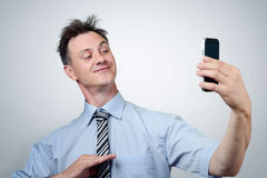 Funny businessman photographing himself on a smartphone Royalty Free Stock Photography