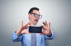 Funny businessman photographing himself on a smartphone Stock Photos
