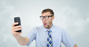 Funny businessman photographing himself on a smartphone Stock Image