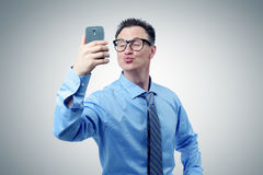 Funny businessman photographing himself on a smartphone Royalty Free Stock Photo