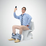 Funny businessman photographing himself in the toilet. Stock Images