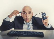 Funny businessman plugging computer mouse to his head internet addict Royalty Free Stock Image