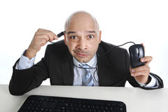 Funny businessman plugging computer mouse to his head internet a Royalty Free Stock Images