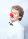 Funny businessman with red clown nose studio shot. Royalty Free Stock Image