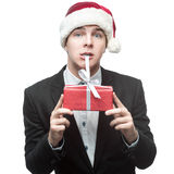 Funny businessman in santa hat biting red gift Stock Photo
