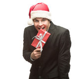 Funny businessman in santa hat biting red gift Stock Image