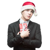 Funny businessman in santa hat holding red gift Royalty Free Stock Photography