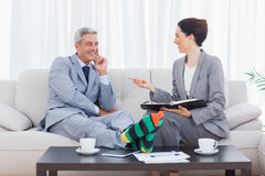 Funny businessman wearing stripey socks and laughing with his co Stock Photography