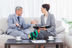 Funny businessman wearing stripey socks and talking with his col. League sitting on sofa royalty free stock images