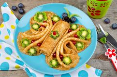 Funny Butterfly face pancakes with berries and fruits for kids`. Snack food. Creative breakfast idea for kids royalty free stock photos