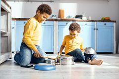 Cheerful little kids drumming on saucepans in kitchen. Funny cacophony. Upbeat little kids sitting on the kitchen floor and drumming on saucepans, pretending to Royalty Free Stock Images