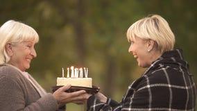 Funny cake joke, happy senior woman congratulating female friend on birthday stock photo
