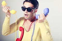 Funny call center guy with colorful phones Stock Image