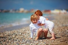 Funny candid moment of kid catching his little baby brother, when he`s falling, family summer vacation Stock Photo