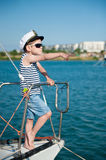 Funny captain child points the direction with his finger standing aboard ship Stock Photos