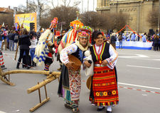 Funny Carnival people. Amused woman with baby doll and man dressed in traditional old female clothes part of mummer group in ornate costumes at Varna Carnival Royalty Free Stock Photos