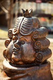 Funny cartoon king, wearing a wig and a crown, bronze statue. Khabarovsk, Russia - May 9, 2017: Fairy tale character metal sculpture face close-up. Chubby Stock Image