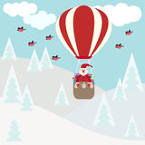 Funny cartoon winter holidays card with Santa flying in hot air Stock Photos