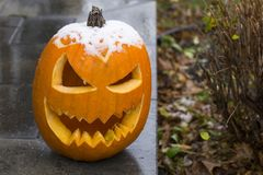Free Funny Carved Pumpkin Left Over From Halloween Seen On Front Step With Snow Cap Royalty Free Stock Images - 163376789